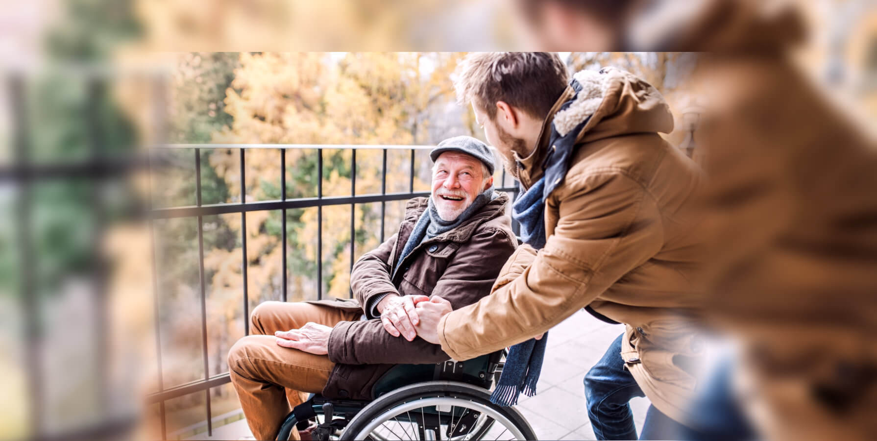 caregiver and elderly man in a wheelchair looking at each other