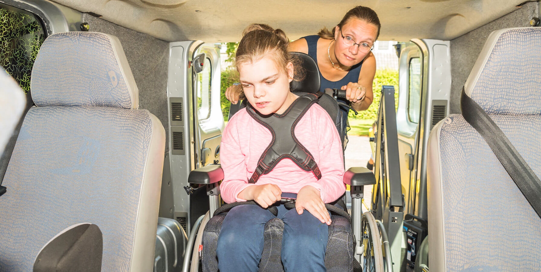 girl in a wheelchair together with a caregiver on a vehicle