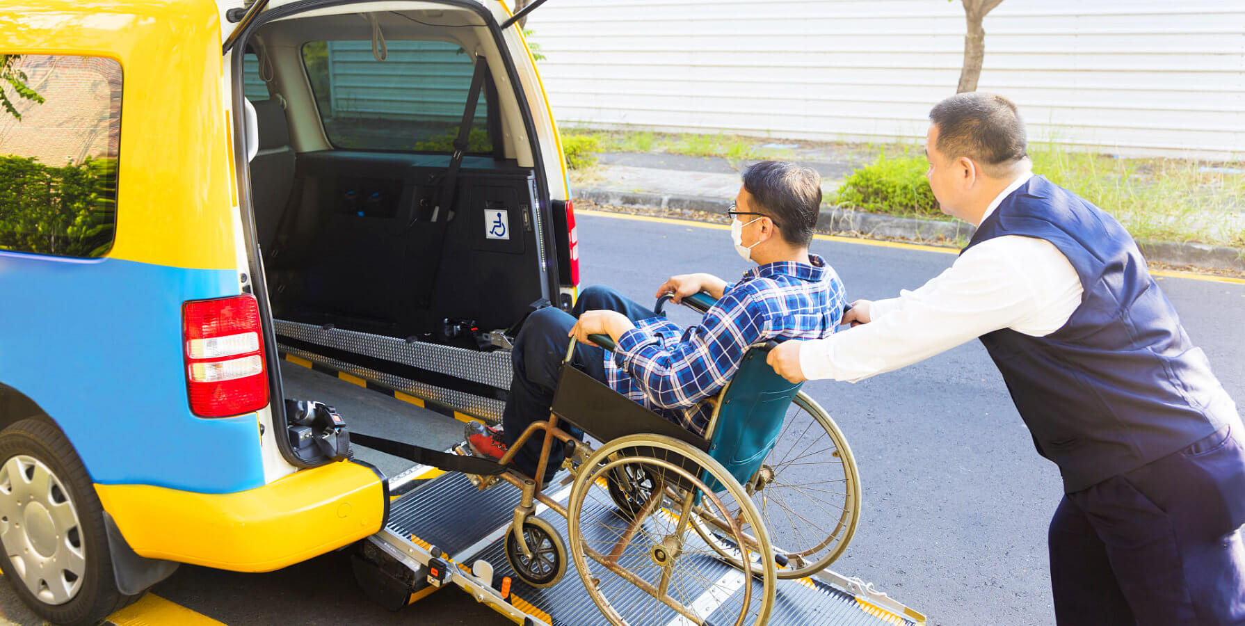 caregiver assisting elderly get into the vehicle