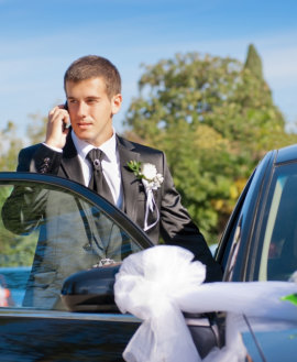 man using phone while entering wedding car